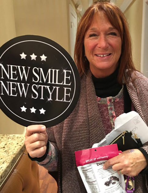 patient holding up new smile new style sign