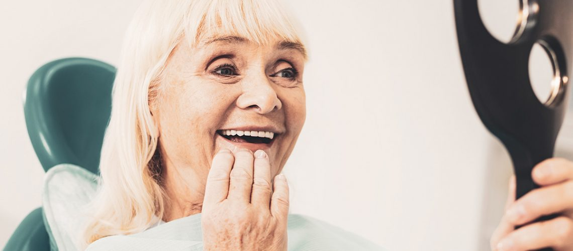 older woman looking at her teeth in the mirror